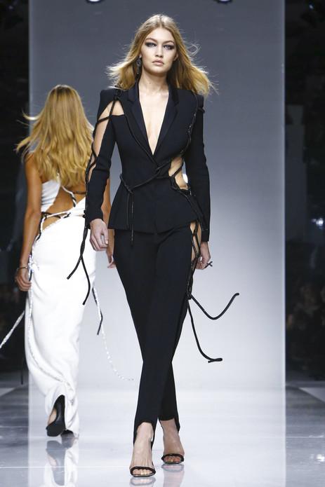 本季的Versace Atelier似乎让我们重新见识了她骨子里性感,大量的工字、T字和Y字的系脖设计恣意挑逗,不对称的切割剪裁可以感受到撕扯的力量。我们又见到了标志性的漆皮,泼上油漆般的色彩令人过目不忘。运动元素显而易见,廓形的棒球夹克,穿插着错综复杂的线条,绝妙之处则在于用勾扣将线条衔接。缠绕的绑带,以及随着身体摆动的抽绳都在用力鞭打着我们的心。而这一季最令人惊喜的则是针织的加入,用彩色的线丝勾勒出完美的身段,将性感发挥到极致,与各种面料的拼接都能激起耀眼的火光。碎裂的几何分割和别出心裁的镂空设计把我们拽到遥远的外太空。