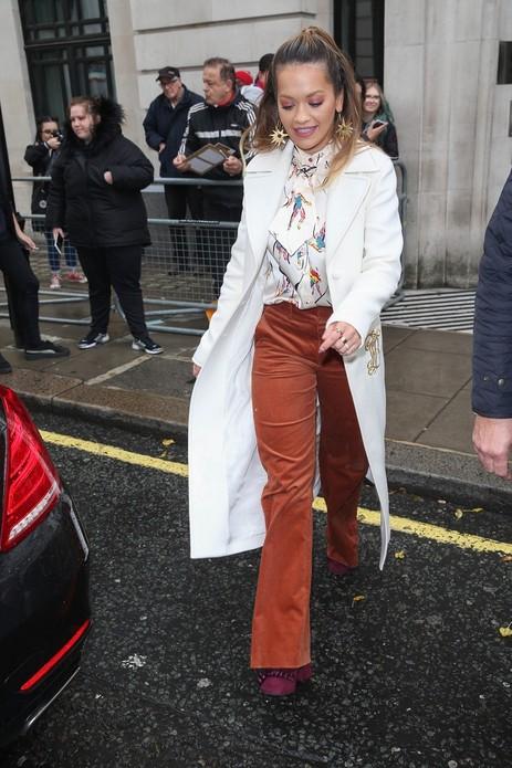 英国歌手Rita Ora身穿Tory Burch 2017秋冬系列象牙白色长款大衣搭配印花衬衫和砖红色长款阔腿裤,脚踩复古酒红色高跟长靴。