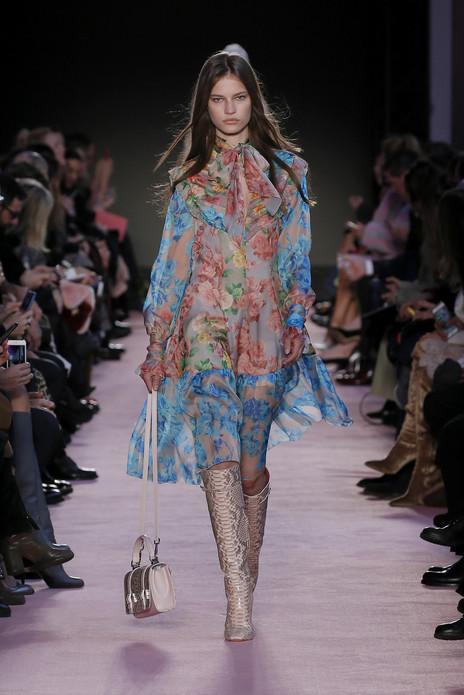 随性之感和女性自我觉知弥漫于Blumarine2018年秋冬新季之中。以极具直觉的混搭理念,设计师擅长的轻盈和浪漫被赋予全新视角。线条和材质自然交缠融合,空灵与魅惑巧妙结合,绝对的精致中是漫不经心的优雅。全新系列轮廓瘦削而柔软:轻盈长裙,短夹克搭配高腰长裤,修身外衣,悦动的裙角。玫瑰,Blumarine的标志,灵动于意想不到的材质之上,打造极具视觉性的纹理:为羊皮夹克和呢大衣平添浪漫,薄纱幻化为触手可得的画作。鹳鸟羽毛随着凤尾裙的褶边飘动,或蔓延于柔美外套之上。柔软单品与坚挺金属质感面料混合,以运动衫式剪裁增添结构之感。蛇皮长靴点缀多个造型,宣扬Blumarine女性在被世人所见的精致外表之下,是绝对勇敢而坚定的强大内心。纹理和色彩相互嬉戏:调色板中的雪纺绸,薄纱,针织和羊毛由淡淡的中性色彩逐渐增强为深邃的午夜蓝,辅以金属色点缀增添闪耀魅力。