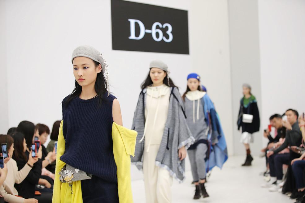 """来自美国的时尚潮牌D-63以""""游走旋律""""为主题,以20世纪70年代纽约的布鲁克林文化为灵感,以无龄感、无界限、无束缚的品牌精神拓展时尚视野,将如明星般耀眼的产品设计,诉诸于独特的视觉语言,演绎都市精英群体""""自由出行,释放真我""""的穿着态度。D-63正是以这样一群都市精英的生活方式、精神诉求为灵感,自由游走于街头潮流、高级时装、复古情怀之间,将个性张扬的街头艺术、涂鸦艺人的前卫创意、时尚手作的文艺情怀与颠覆常规的朋克造型融入设计。同时,结合美式多元化的混搭风格、饱和跳跃的高纯度色彩、精雕细琢的高定手工艺技术、颠覆传统的创新科技感面料,将时装与艺术、艺术与生活再定义,重组合,最终打造出更自由、更新潮、更具个性化的明星出行着装。两大时装品牌,一个时尚文艺,一个新锐潮流,同一时间,同一地点,深圳时装周,激燃瞳孔。"""